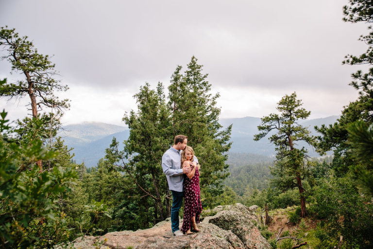 Morrison engagement session at Mount Falcon Park, couple standing on a rock embracing each other